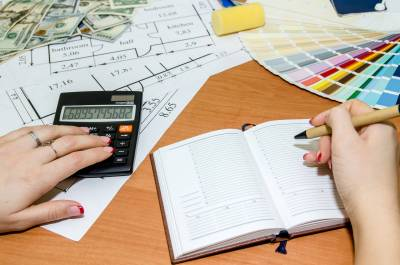 architectural plans with palette of colors, money, calculator, notepad